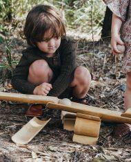 boy-playing-bush-bamboo-construct-roll-handmade-kids-toys-play